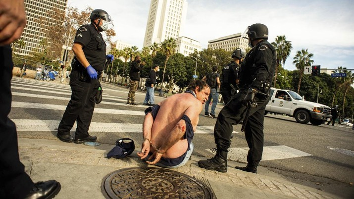 A Trump supporter is detained by LAPD officers after a brawl with counter protesters  in Los Angeles on Wednesday, Jan. 6, 2021. (Sarah Reingewirtz/The Orange County Register via AP)
