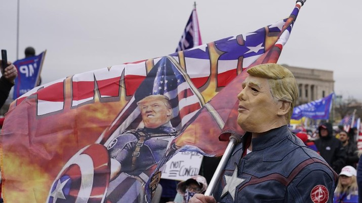 Robert Ramsey of Tulsa, Okla., wears a Trump mask at a rally at the Oklahoma Capitol, Wednesday, Jan. 6, 2021, in Oklahoma City. (AP Photo/Sue Ogrocki)