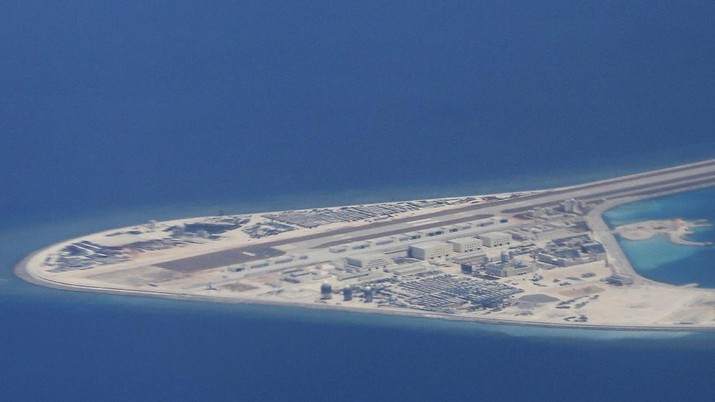 FILE - In this Friday, April 21, 2017, file photo, an airstrip, structures and buildings on China's man-made Subi Reef in the Spratly chain of islands in the South China Sea are seen from a Philippine Air Force C-130 transport plane of the Philippine Air Force. (AP Photo/Bullit Marquez, File)