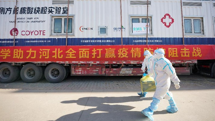 In this photo released by China's Xinhua News Agency, workers carry a container of coronavirus test samples outside of a residential neighborhood in Shijiazhuang in northern China's Hebei Province, Friday, Jan. 8, 2021. A city in northern China is offering rewards of 500 yuan ($77) for anyone who reports on a resident who has not taken a recent coronavirus test. The offer from the government of Nangong comes as millions in the city and its surrounding province of Hebei are being tested as part of efforts to control China's most serious recent outbreak of COVID-19.(Mu Yu/Xinhua via AP)
