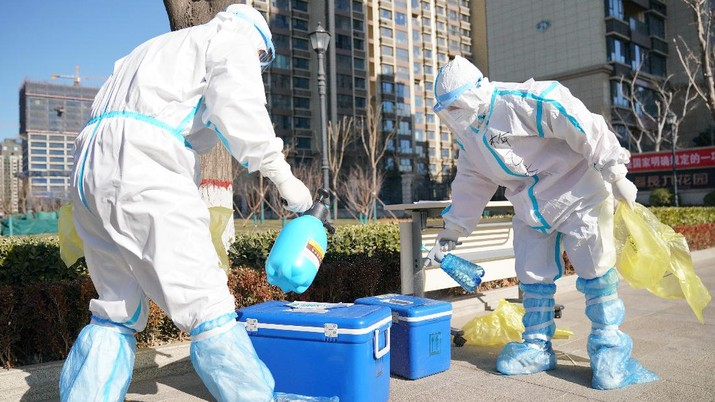 In this photo released by China's Xinhua News Agency, workers disinfect containers of coronavirus test samples outside of a residential neighborhood in Shijiazhuang in northern China's Hebei Province, Friday, Jan. 8, 2021. A city in northern China is offering rewards of 500 yuan ($77) for anyone who reports on a resident who has not taken a recent coronavirus test. The offer from the government of Nangong comes as millions in the city and its surrounding province of Hebei are being tested as part of efforts to control China's most serious recent outbreak of COVID-19.(Mu Yu/Xinhua via AP)