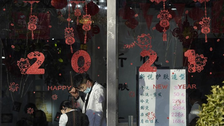 Employees stand near new year decorations at a beauty saloon in Beijing on Friday, Jan. 8, 2021. With next month's Lunar New Year travel rush looming, the government is telling people to stay put as much as possible and not travel to or from the capital Beijing. (AP Photo/Ng Han Guan)
