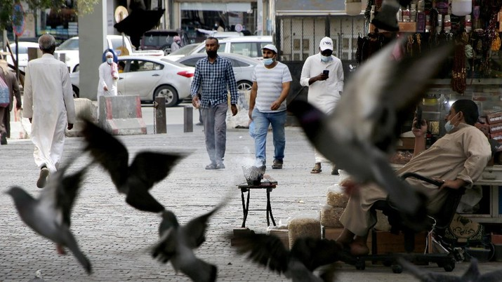 People wearing face masks to help curb the spread of the coronavirus, as they walk at Jiddah old city, Saudi Arabia, Thursday, Dec. 17, 2020. (AP Photo/Amr Nabil)