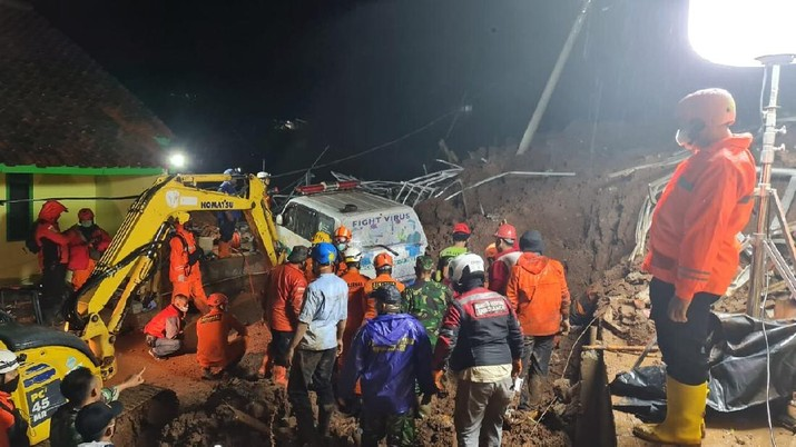 In this photo provided by the Indonesian National Disaster Mitigation Agency, rescuers work the scene of a landslide in Cihanjuang village, Indonesia, early Sunday, Jan. 10, 2021. Two landslides in the Sumedang district of West Java province triggered by heavy rain in Indonesia left multiple people dead and injured, officials said Sunday.  (Indonesian National Disaster Mitigation Agency via AP)