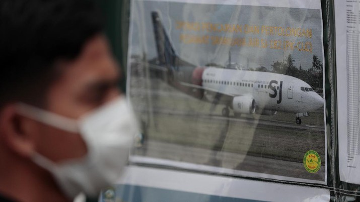 A man walks past a picture of Sriwijaya Air's passenger jet that crashed off Java island, put up at the command center for the search and rescue mission at Tanjung Priok Port in Jakarta, Indonesia, Sunday, Jan. 10, 2021. Indonesian rescuers pulled out body parts, pieces of clothing and scraps of metal from the Java Sea early Sunday morning, a day after a Boeing 737-500 with dozens of people onboard crashed shortly after takeoff from Jakarta, officials said. (AP Photo/Dita Alangkara)