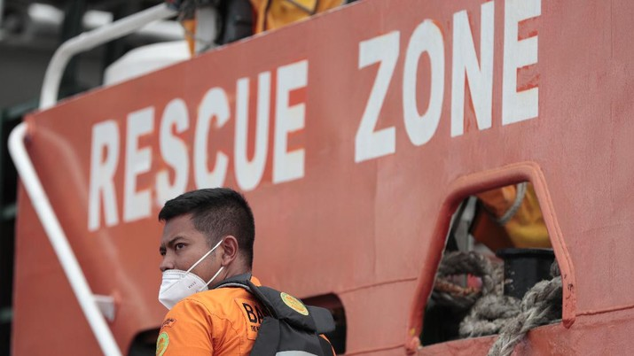 A Member of Nationl Search and Rescue Agency (BASARNAS) stands on a rescue ship prepared for a search for Sriwijaya Air's passenger jet that crashed off Java island, at Tanjung Priok Port in Jakarta, Indonesia, Sunday, Jan. 10, 2021. Indonesian rescuers pulled out body parts, pieces of clothing and scraps of metal from the Java Sea early Sunday morning, a day after a Boeing 737-500 with dozens of people onboard crashed shortly after takeoff from Jakarta, officials said. (AP Photo/Dita Alangkara)