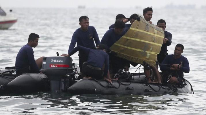 Penyelam Angkatan Laut Indonesia menarik sebagian dari pesawat keluar dari air selama operasi pencarian jet penumpang Sriwijaya Air yang jatuh ke laut dekat Jakarta, Indonesia, Minggu, 10 Januari 2021.(AP Photo/Achmad Ibrahim)