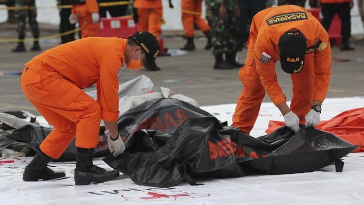Tim penyelamat membawa kantong jenazah berisi jasad manusia yang ditemukan dari perairan tempat jet penumpang Sriwijaya Air jatuh, di Pelabuhan Tanjung Priok di Jakarta, Indonesia, Minggu, 10 Januari 2021.(AP Photo/Tatan Syuflana)