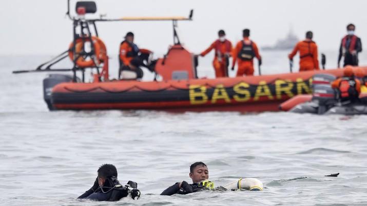 Penyelam Angkatan Laut Indonesia menarik sebagian dari pesawat keluar dari air selama operasi pencarian jet penumpang Sriwijaya Air yang jatuh ke laut dekat Jakarta, Indonesia, Minggu, 10 Januari 2021. (AP Photo/Achmad Ibrahim)