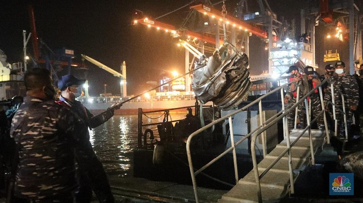 Prajurit TNI AL menurunkan bagian mesin turbin pesawat Sriwijaya Air SJ182 rute Jakarta-Pontianak dari KRI Cucut (886) di Dermaga JICT, Tanjung Priok, Jakarta, Minggu (10/1/2021). (CNBC Indonesia/ Andrean Kristianto)
