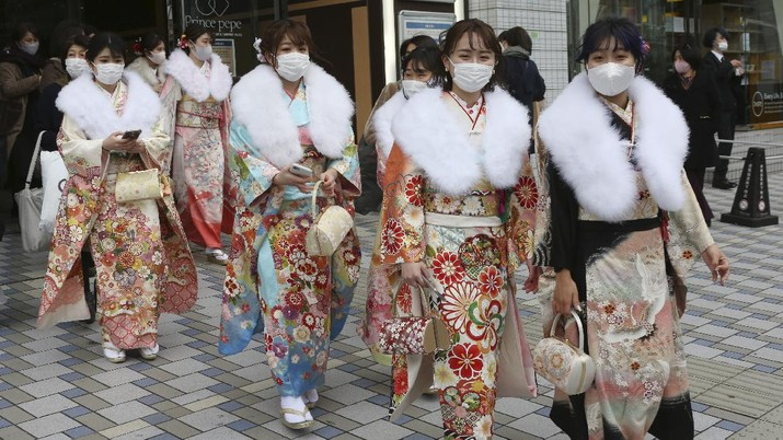 Kimono-clad women wearing face masks to protect against the spread of the coronavirus walk out after a Coming-of-Age ceremony in Yokohama, near Tokyo, Monday, Jan. 11, 2021. The Tokyo area has been under a state of emergency since Friday to try to stop the spread of the virus. (AP Photo/Koji Sasahara)