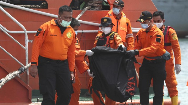 Rescuers carry debris found in the waters around the location where Sriwijaya Air passenger jet crashed at Tanjung Priok Port in Jakarta, Indonesia, Monday, Jan. 11, 2021. The search for the black boxes of a crashed Sriwijaya Air jet has intensified to boost the investigation into what caused the plane carrying dozens of people to nosedive into Indonesia seas. The Boeing 737-500 jet disappeared during heavy rain on Saturday. (AP Photo/Achmad Ibrahim)