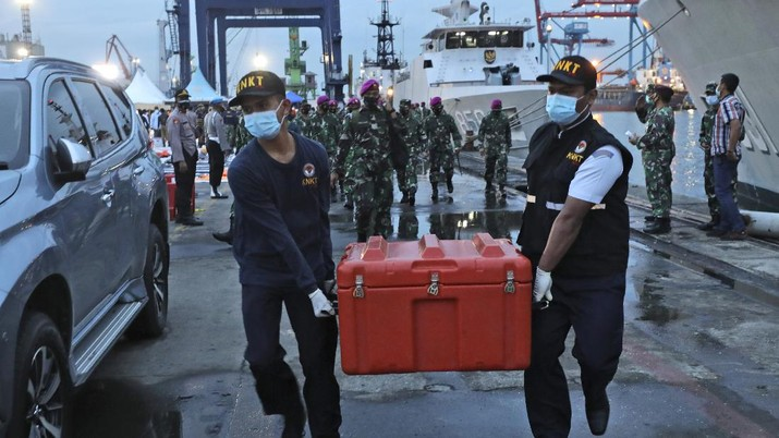 Members of the National Transportation Safety Committee carry a box containing the flight data recorder of Sriwijaya Air flight SJ-182 retrieved from the Java Sea where the passenger jet crashed at the Tanjung Priok Port, Tuesday, Jan. 12, 2021. Indonesian navy divers searching the ocean floor on Tuesday recovered the flight data recorder from a Sriwijaya Air jet that crashed into the Java Sea with 62 people on board, Monday, Jan. 11, 2021. (AP Photo/Dita Alangkara)