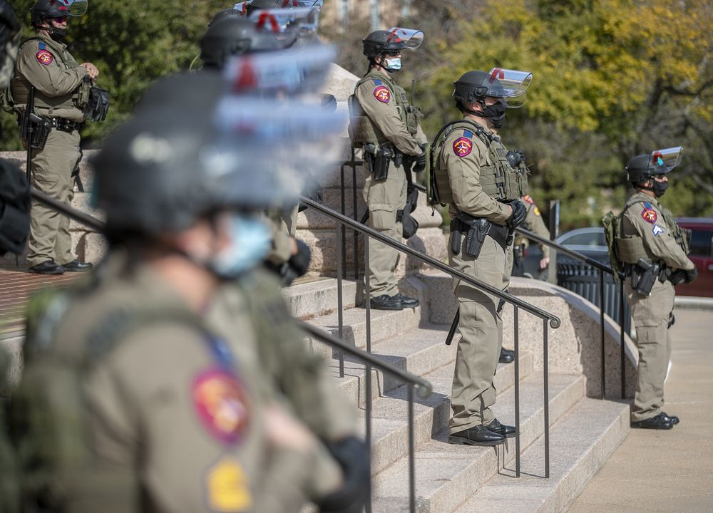 DPS state troopers and the National Guard protect the Capitol on the first day of the 87th Legislature, Tuesday Jan. 12, 2021 in Austin, Texas. More than 100 Texas troopers, including dozens wearing tactical vests and carrying riot gear, stood on guard outside the state Capitol on Tuesday as lawmakers returned to work amid FBI warnings of armed protests at statehouses across the country. (Ricardo B. Brazziell/Austin American-Statesman via AP)