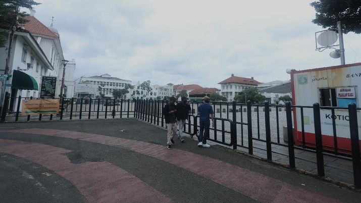 Sejumlah warga melewati Jalan Pintu Besar Utara yabg ditutup di kawasan Kota Tua, Jakarta, Rabu (13/1/2021). Pemerintah Kota Administrasi Jakarta Barat menutup sejumlah ruas jalan menuju kawasan wisata Kota Tua selama Pemberlakuan Pembatasan Kegiatan Masyarakat (PPKM) di DKI Jakarta pada 11 Januari hingga 25 Januari 2021 untuk mencegah kerumunan. (CNBC Indonesia/Tri Susilo) Pantauan CNBC Indonesia kemacetan tidak terhindarkan kendaraan dari arah Harmoni menuju Jalan Pintu Besar Utara karena banyak pengguna jalan yang belum mengetahui penutupan jalur.  Salah satu satgas Kota Tua yang tidak ingin disebutkan namanya mengatakan