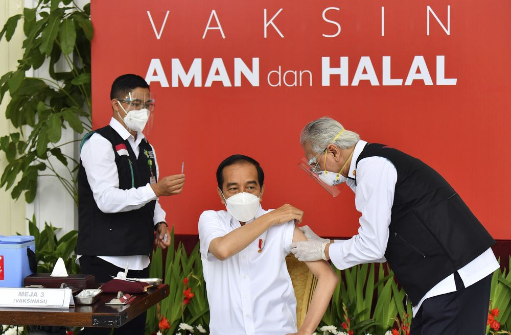 In this photo released by the Indonesian Presidential Palace, President Joko Widodo prepares to receive a shot of COVID-19 vaccine at Merdeka Palace in Jakarta, Indonesia, Wednesday, Jan. 13, 2021. Widodo on Wednesday received the first shot of a Chinese-made COVID-19 vaccine after Indonesia approved it for emergency use and began efforts to vaccine millions of people in the world's fourth most populated country. Writings on the banner in the background read