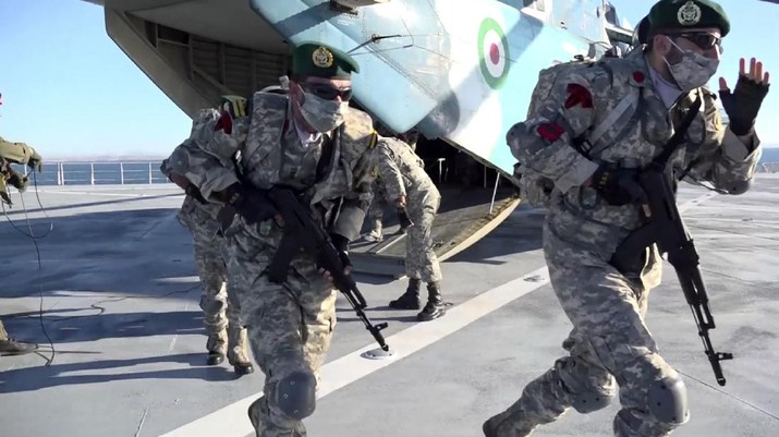 This image made from a video released on Wednesday, Jan. 13, 2021, by the Iranian Army shows troops leaving a helicopter on Makran logistics vessel during a navy drill. Iran's navy began a short-range missile drill in the Gulf of Oman on Wednesday, state TV reported, amid heightened regional tensions over Tehran's nuclear program and a U.S. pressure campaign against the Islamic Republic. (Iranian Army via AP)