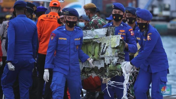 Petugas Basarnas menurunkan kantong jenazah dan puing korban pesawat Sriwijaya Air SJ182 yang jatuh di perairan Kepulauan Seribu, Kamis (14/1/2021). Selanjutnya tim Basarnas menyerahkan beberapa kantong jenazah yang telah dikumpulkan kepada Tim DVI dan KNKT untuk pemeriksaan (CNBC Indonesia/ Tri Susilo)
