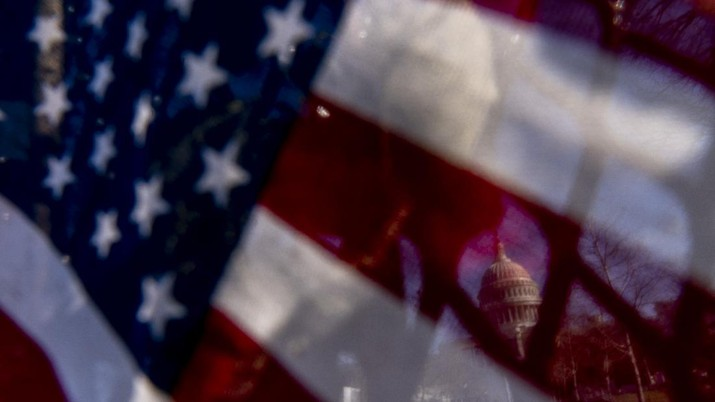 The dome of the U.S. Capitol is visible through an American flag placed on fencing surrounding the Capitol Building on Capitol Hill in Washington, Thursday, Jan. 14, 2021. (AP Photo/Andrew Harnik)