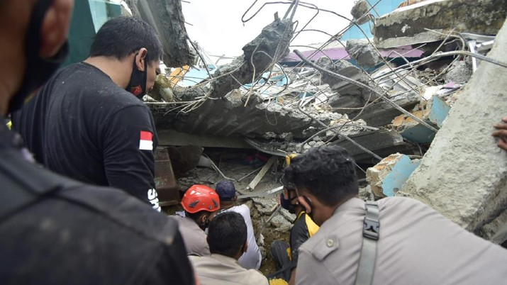 Rescuers search for survivors among the ruin of a building damaged by an earthquake in Mamuju, West Sulawesi, Indonesia, Friday, Jan. 15, 2021. A strong, shallow earthquake shook Indonesia's Sulawesi island just after midnight Friday, toppling homes and buildings, triggering landslides. (AP Photo/Daus Thobelulu)