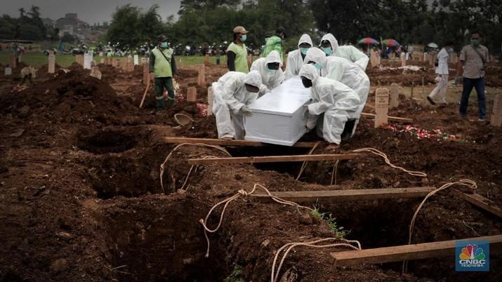 Petugas membawa peti jenazah yang akan dimakamkan dengan protokol COVID-19 di area khusus TPU Srengseng Sawah, Jakarta, Jumat (15/1/2021). TPU Srengseng Sawah mulai menerima pemakaman jenazah dengan protokol COVID-19 sejak Selasa (12/1) lalu. Menurut petugas makam dalam tiga hari terakhir sudah 164 jenazah Covid-19 yang dikubur di TPU tersebut. Lahan pemakaman di Pondok Rangon dan Tegal Alur yang saat ini menjadi lahan pemakaman pasien Corona Virus Desease 2019 (COVID-19) yang hampir penuh. Meski untuk jenazah pasien Covid 19, jenazah non Covid-19 masih bisa digunakan untuk pemakaman. Pantauan CNBC Indonesia sampai pukul 14.00 wib sudah 20 jenazah yang dimakamkan, dan kemungkinan akan bertambah lagi. Ada empat TPU di wilayah Jakarta yang digunakan untuk memakamkan jenazah pasien Covid-19, yakni TPU Tegal Alur di Jakarta Barat, TPU Pondok Ranggon di Jakarta Timur, TPU Rorotan di Jakarta Utara, dan TPU Srengseng Sawah. Dikutip dari CNN Indonesia pada Kamis, 14/1, Kepala Suku Dinas Pertamanan dan Hutan Kota Jakarta Selatan Winarto mengatakan, lahan di TPU Srengseng Sawah digunakan untuk memakamkan jenazah Covid-19 muslim. Dalam menangani krisis lahan pemakaman ini, pihak TPU Pondok Ranggon maupun TPU Tegal Alur juga menerapkan makam tumpang. Namun, mekanisme tersebut harus mendapat izin pihak keluarga. (CNBC Indonesia/ Muhammad Sabki)