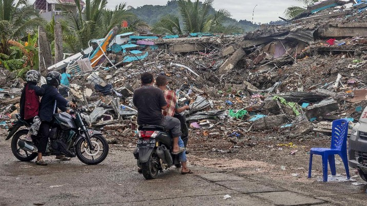 People look at the ruin of a building flattened during an earthquake in Mamuju, West Sulawesi, Indonesia, Saturday, Jan. 16, 2021. Damaged roads and bridges, power blackouts and lack of heavy equipment on Saturday hampered Indonesia's rescuers after a strong and shallow earthquake left a number of people dead and injured on Sulawesi island. (AP Photo/Yusuf Wahil)