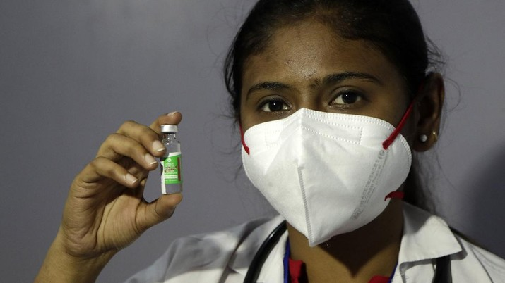 A health worker shows COVID-19 vaccine in Mumbai, India, Saturday, Jan. 16, 2021. India started inoculating health workers Saturday in what is likely the world's largest COVID-19 vaccination campaign, joining the ranks of wealthier nations where the effort is already well underway. (AP Photo/Rajanish Kakade)
