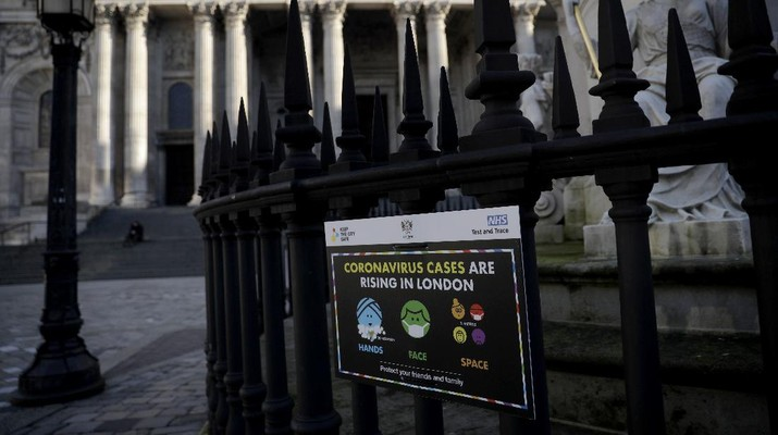 A coronavirus warning sign is displayed outside St. Paul's Cathedral, in the City of London financial district of London, Friday, Jan. 22, 2021, during England's third national lockdown since the coronavirus outbreak began. The U.K. is under an indefinite national lockdown to curb the spread of the new variant, with nonessential shops, gyms and hairdressers closed, most people working from home and schools largely offering remote learning. (AP Photo/Matt Dunham)