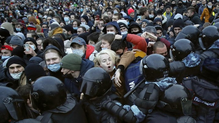 People clash with police during a protest against the jailing of opposition leader Alexei Navalny in St.Petersburg, Russia, Saturday, Jan. 23, 2021. Russian police on Saturday arrested hundreds of protesters who took to the streets in temperatures as low as minus-50 C (minus-58 F) to demand the release of Alexei Navalny, the country's top opposition figure. A Navalny, President Vladimir Putin's most prominent foe, was arrested on Jan. 17 when he returned to Moscow from Germany, where he had spent five months recovering from a severe nerve-agent poisoning that he blames on the Kremlin. (AP Photo/Dmitri Lovetsky)