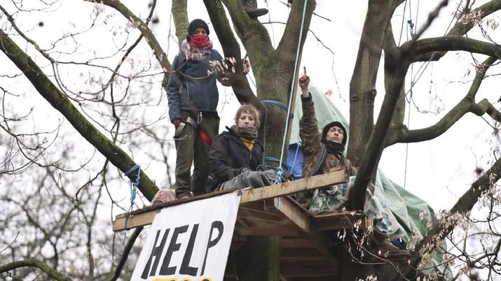 Para pengunjuk rasa duduk di atas pepohonan di perkemahan di Euston Square Gardens di pusat kota London, Inggris, Rabu (27/1/2021). (AP/Aaron Chown)