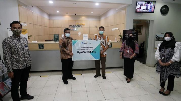 (Ki-Ka) Perwakilan AXA Mandiri mendampingi Area Manager Surabaya Kota Mandiri Syariah Edi Dwi Efendi, menyerahkan secara simbolis klaim biaya perawatan COVID-19 senilai lebih dari Rp 460 juta kepada penyintas COVID-19 Syamsul Hariadi di Surabaya, 28 Januari 2021. Syamsul merupakan pemegang polis Asuransi Mandiri Perlindungan Sejahtera Syariah. (Dok: Mandiri)