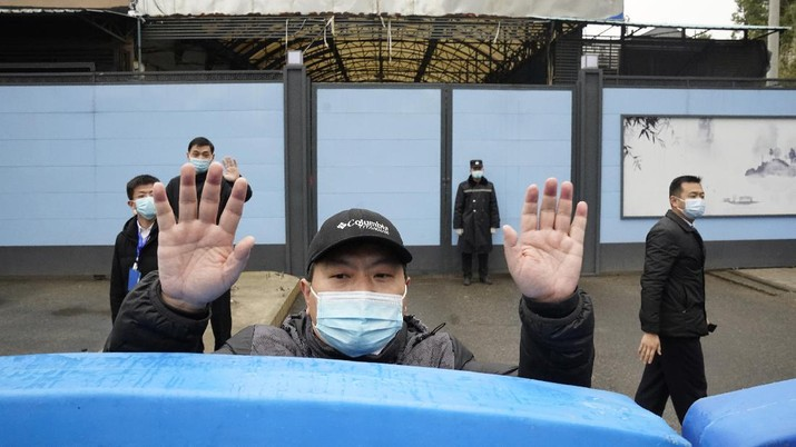 A security guard waves for journalists to clear the road after a convoy carrying the World Health Organization team entered the Huanan Seafood Market on the third day of a field visit in Wuhan in central China's Hubei province on Sunday, Jan. 31, 2021. Scientists initially suspected the coronavirus came from wild animals sold in the market. The market has since been largely ruled out but for the visiting WHO team of international researchers it could still provide hints to how the virus spread so widely. (AP Photo/Ng Han Guan)