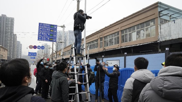 A photographer on a tall ladder tries to shoot photos of the World Health Organization convoy after it entered the Huanan Seafood Market on the third day of field visit in Wuhan in central China's Hubei province on Sunday, Jan. 31, 2021. Scientists initially suspected the coronavirus came from wild animals sold in the market. The market has since been largely ruled out but for the visiting WHO team of international researchers it could still provide hints to how the virus spread so widely. (AP Photo/Ng Han Guan)