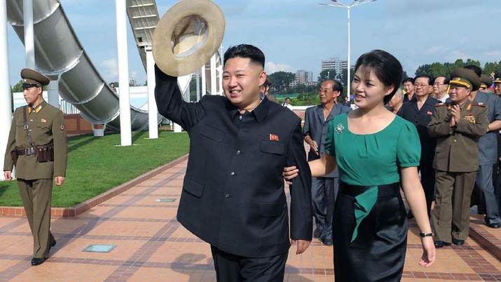 In this Wednesday, July 25, 2012 photo released by the Korean Central News Agency (KCNA) and distributed in Tokyo by the Korea News Service Thursday, July 26, 2012, North Korean leader Kim Jong Un, center, accompanied by his wife Ri Sol Ju, right, waves to the crowd as they inspect the Rungna People's Pleasure Ground in Pyongyang. (AP Photo/Korean Central News Agency via Korea News Service) JAPAN OUT UNTIL 14 DAYS AFTER THE DAY OF TRANSMISSION