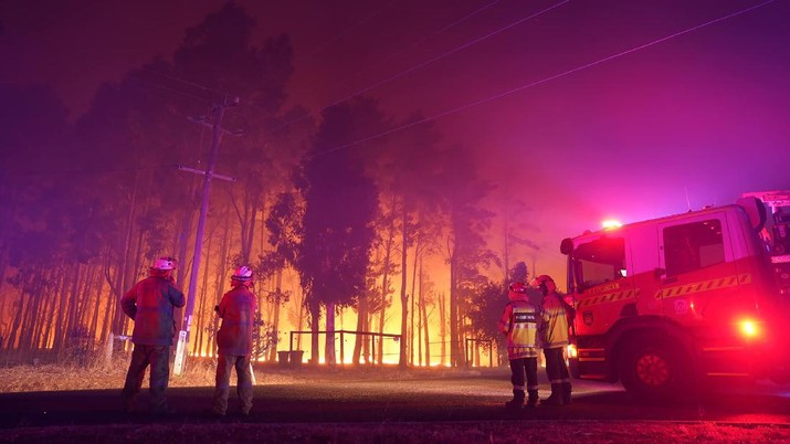 Firefighters attend a fire at Wooroloo, near Perth, Australia, Monday, Feb. 1, 2021. An out-of-control wildfire burning northeast of the Australian west coast city of Perth has destroyed an estimated 30 homes and was threatening more Tuesday, with many locals across the region told it is too late to leave. (Evan Collis/DFES via AP)