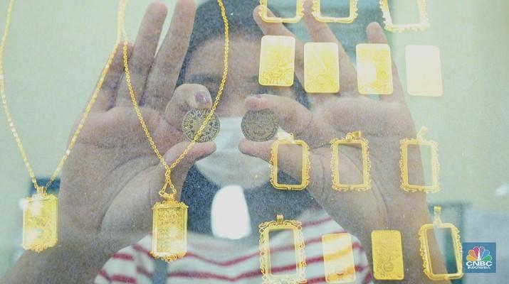 Petugas menunjukkan koin emas Dirham di Gerai Butik Emas Antam, Jakarta, Kamis (4/2/2021). Bank Indonesia (BI) mengajak masyarakat dan berbagai pihak untuk menjaga kedaulatan Rupiah sebagai mata uang NKRI.    (CNBC Indonesia/ Tri Susislo)