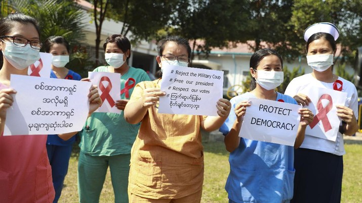 Staffers of the University Hospital hold signs that read