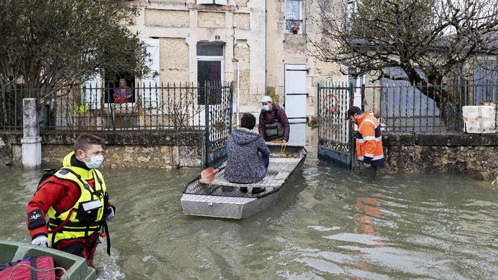 A rescue worker, left, and volunteers help residents in a flooded street of Le Gond-Pontouvre, near Angouleme, southwestern France, Friday, Feb 5, 2021. In southern France, waters are starting to recede after the worst flooding in 40 years swelled the Garonne River between Bordeaux and Toulouse. (AP Photo/Yohan Bonnet)