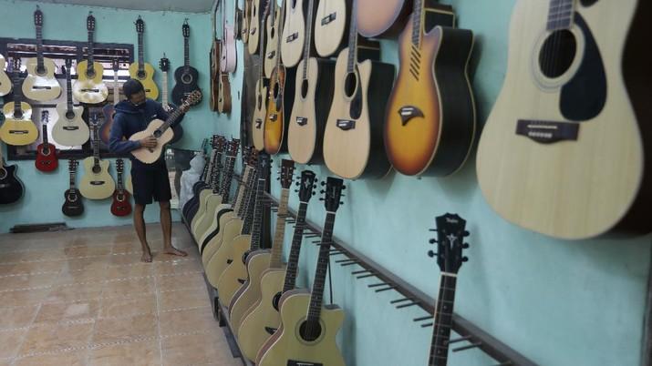Pengrajjn  memperbaiki gitar pelanggan di servis gitar pak Manto, Jakarta Selatan, Senin (8/2/2021). Selain mereparasi gitar, Manto juga memproduksi gitar akustik yang dijual dari harga ratusan ribu hingga juta, tergantung jenis dan tingkat kesulitannya. (CNBC Indonesia/Andrean Kristianto)