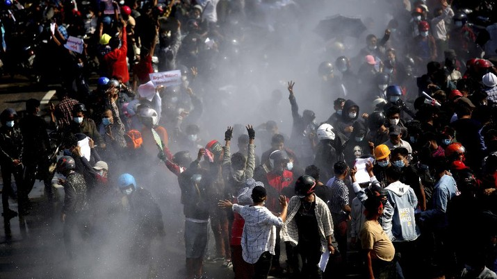Protesters are sprayed with water fired from a police truck's water cannon in Naypyitaw, Myanmar on Monday, Feb. 8, 2021. Tension in the confrontations between the authorities and demonstrators against last week's coup in Myanmar boiled over Monday, as police fired a water cannon at peaceful protesters in the capital Naypyitaw.(AP Photo)