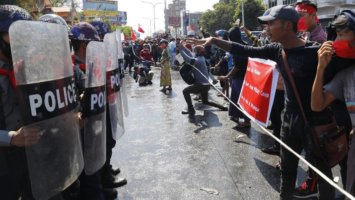 Protesters regroup after police fired warning-shots and used a water cannon to disperse them during a protest in Mandalay, Myanmar on Tuesday, Feb. 9, 2021. Police cracked down Tuesday on the demonstrators protesting against Myanmar's military takeover who took to the streets in defiance of new protest bans. (AP Photo)