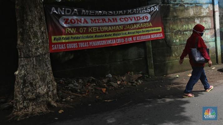 Warga melintas di wilayah Zona Merah di Kawasan Jagakarsa, Jakarta Selatan, Selasa (9/2/2021). Aturan mengenai PPKM Mikro yang berlaku mulai 9 Februari 2021 telah diterbitkan lewat Inmendagri 3 Tahun 2021. (CNBC Indonesia/Andrean Kristianto)