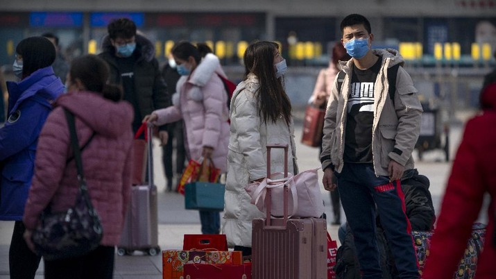 Travelers wearing face masks to protect against the coronavirus walk with their luggage outside the Beijing Railway Station in Beijing, Wednesday, Feb. 10, 2021. China appeared to be on pace for a slower than normal Lunar New Year travel rush this year after authorities discouraged people from traveling over the holiday to help maintain the nation's control over the ongoing COVID-19 pandemic. (AP Photo/Mark Schiefelbein)