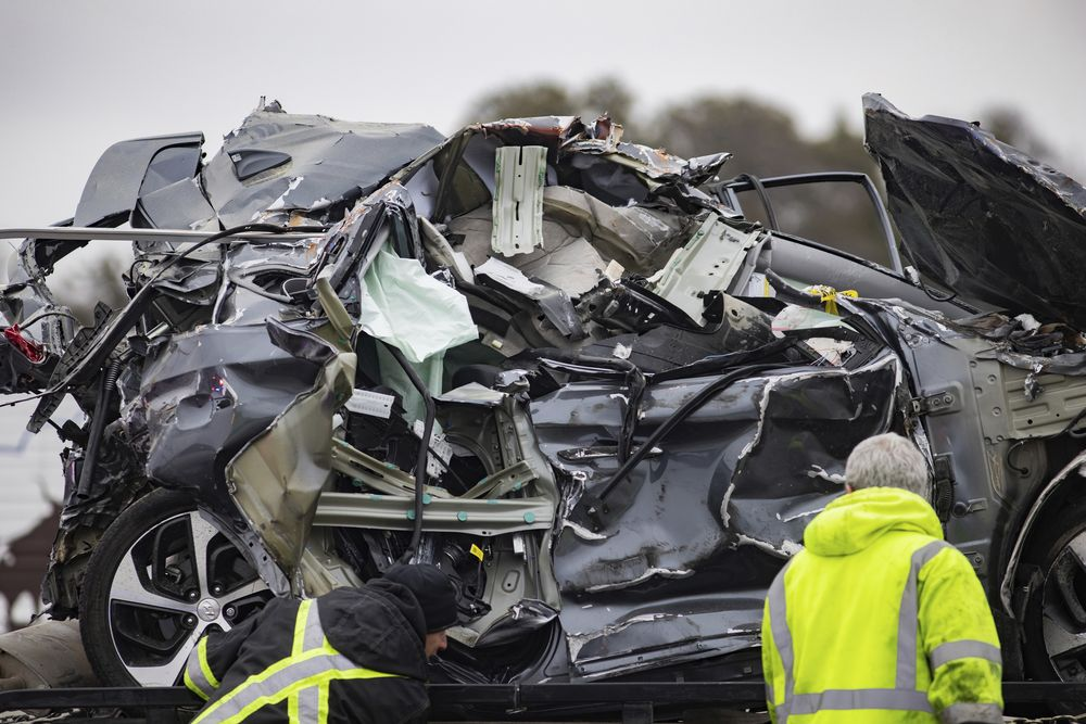 A crumbled car is towed as emergency crews work to clear the pile-up on Interstate 35 in Fort Worth, Texas on Thursday, Feb. 11, 2021. A massive crash involving more than 130 vehicles on the icy Texas interstate left at least six people dead and dozens injured amid a winter storm that dropped freezing rain, sleet and snow on parts of the U.S. (Juan Figueroa/The Dallas Morning News via AP)