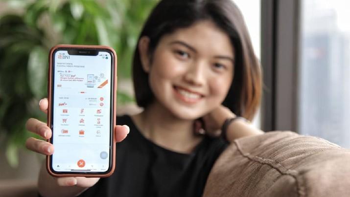 Nasabah milenial menunjukkan aplikasi BNI Mobile Banking pada smartphone. (Dok. BNI)