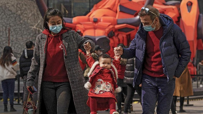 A couple wearing face masks to help curb the spread of the coronavirus lift their child wearing a new year costume as they visit to the capital city's popular shopping mall during the first day of the Lunar New Year in Beijing, Friday, Feb. 12, 2021. Festivities for the holiday, normally East Asia's busiest tourism season, are muted after China, Vietnam, Taiwan and other governments tightened travel curbs and urged the public to avoid big gatherings following renewed virus outbreaks. (AP Photo/Andy Wong)