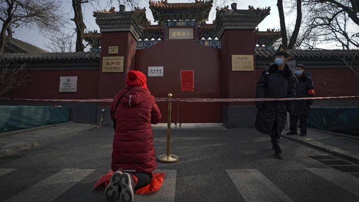 Security guards wearing face masks to help curb the spread of the coronavirus stand watch as a woman offers prayer near a barricade tape outside the closed Yonghegong Lama Temple, usually crowded with worshippers during the first day of the Lunar New Year in Beijing, Friday, Feb. 12, 2021. Festivities for the holiday, normally East Asia's busiest tourism season, are muted after China, Vietnam, Taiwan and other governments tightened travel curbs and urged the public to avoid big gatherings following renewed virus outbreaks. (AP Photo/Andy Wong)