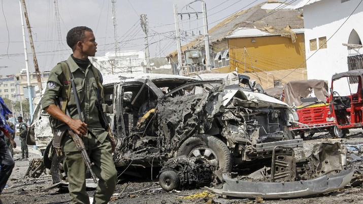 Rescuers at the scene of a bombing in Mogadishu, Somalia Saturday, Feb. 13, 2021. Police say a suicide bomber died and a number of civilians were wounded when a vehicle exploded near a checkpoint outside the presidential palace in Somalia's capital, Mogadishu. (AP Photo/Farah Abdi Warsameh)