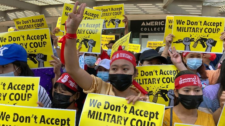 An anti-military coup protester flashes the three-fingered salute while other protesters hold placards that say 'We Don't Accept Military Coup' as they gather outside the Hledan Center in Yangon, Myanmar Saturday, Feb. 13, 2021. The daily protests in Myanmar's biggest city enters its second week despite a ban on public gatherings of five or more. (AP Photo)
