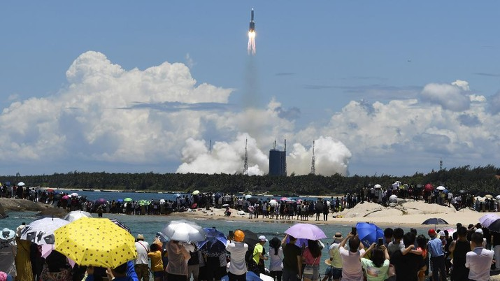 In this July 23, 2020, file photo released by China's Xinhua News Agency, spectators watch as a Long March-5 rocket carrying the Tianwen-1 Mars probe lifts off from the Wenchang Space Launch Center in southern China's Hainan Province. China is falling in love with space, inspired by the ruling Communist Party's increasingly ambitious missions over the past two decades to fire humans into orbit and explore the moon and Mars. (Yang Guanyu/Xinhua via AP, File)